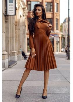Sukienka Doris Carmel-BR03-One Size Karmelowa sukienka z długim rękawem, z uroczą kokardką wiązana pod szyją oraz plisowaną spódnicą Molerin   - kod rabatowy